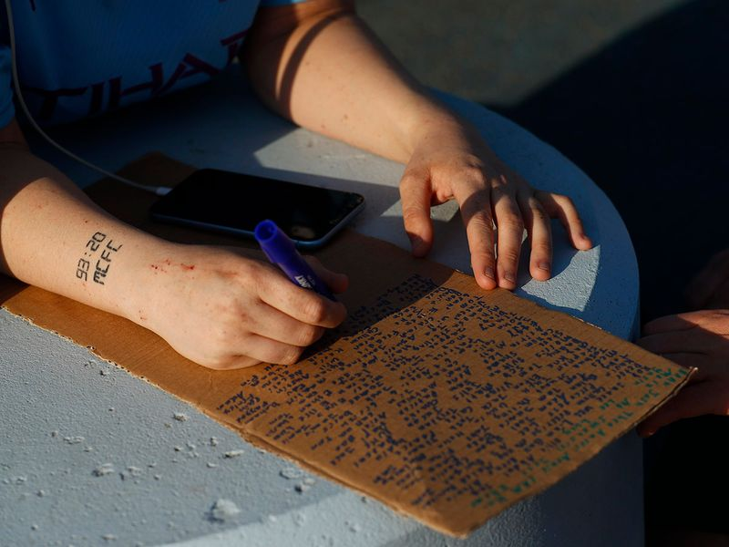 A fan with a Manchester City tattoo signs a petitions against the European Super League.