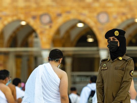 A female soldier stands guard at the Grand Mosque in Mecca.