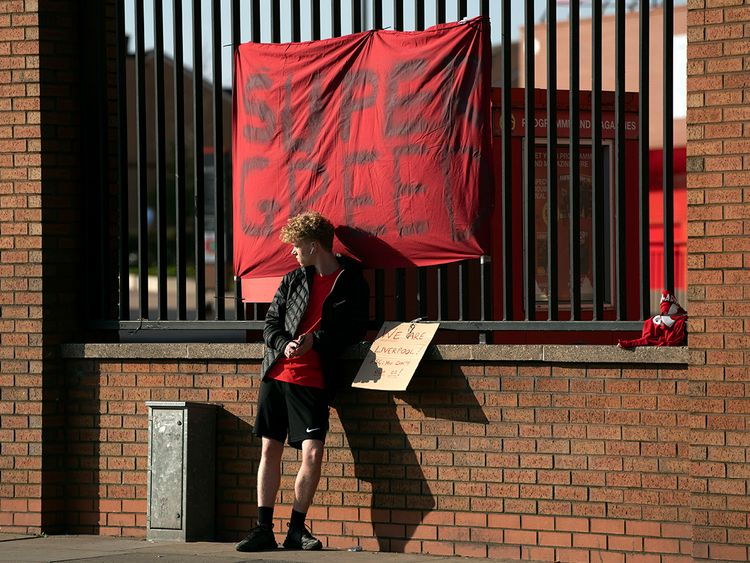 A member of the public stands by a banner outside Liverpool's Anfield Stadium protesting the formation of the European Super League.