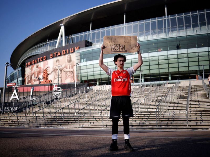 An Arsenal fan stands with his anti-European Super League banner outside the Emirates Stadium, home of English Premier League football club Arsenal.