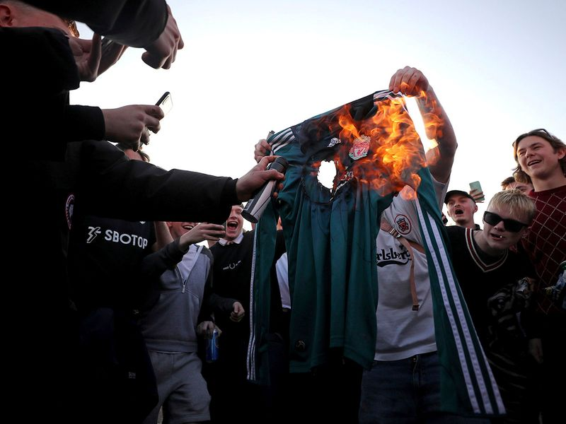 Fans burn replica Liverpool shirt in protest of the European Super League, announced Monday.