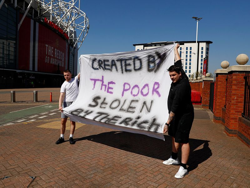Fans hold up signs that say 'created by the poor, stolen by the rich' in protest of Super League.