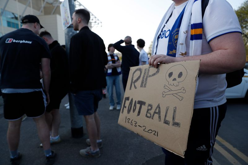 People protest the planned European Super League outside the Leeds stadium before the match. It was announced twelve of Europe's top football clubs will launch a breakaway Super League.