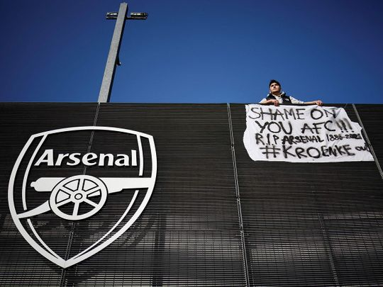 An Arsenal fan stands with his anti-European Super League banner outside the Emirates Stadium on April 19, 2021.