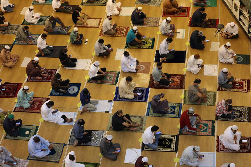 Muslim worshippers maintain social distancing as they pray on the first Friday of the holy fasting month of Ramadan at a mosque in Dubai on April 16, 2021.