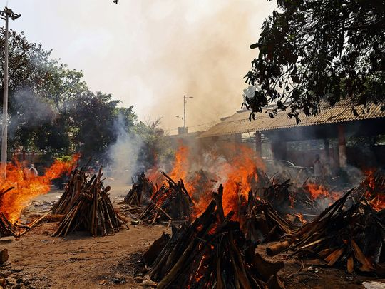 Funeral pyres of COVID-19 fatalities burn at a crematorium in New Delhi