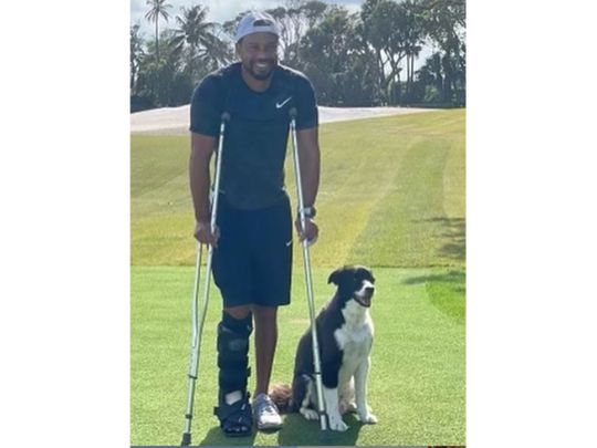 Tiger Woods on his golf course with pet dog Bugs
