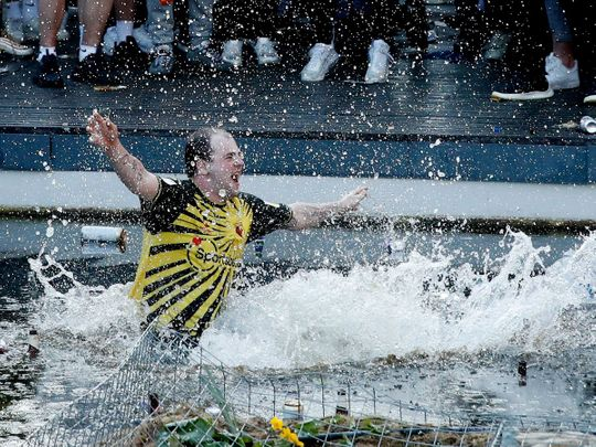 A Watford fan jumps into a fountain after his club sealed promotion to the Premier League