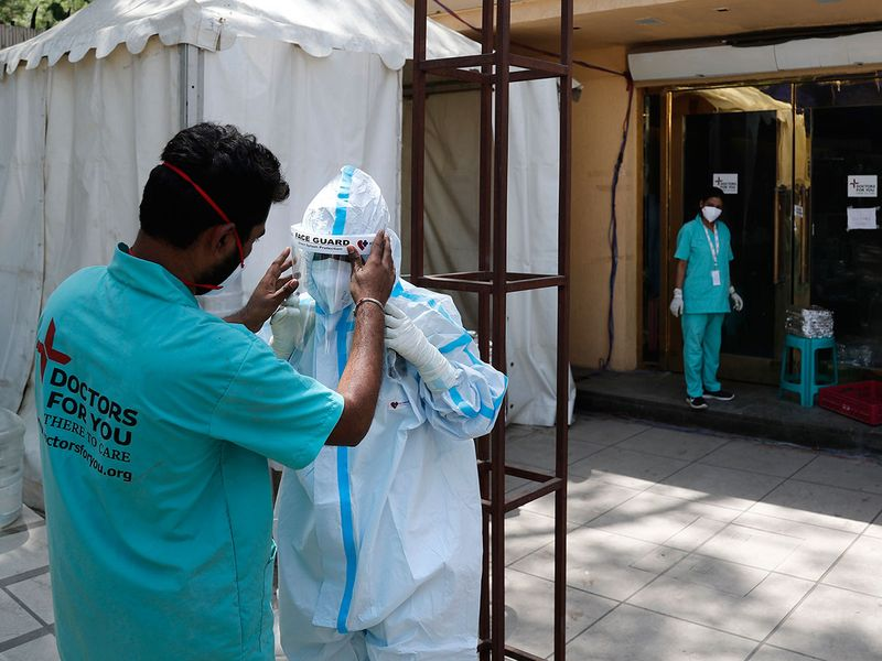 A health worker adjusts the face shield of another as she prepares to go inside a quarantine center for COVID-19 patients in New Delhi, India.