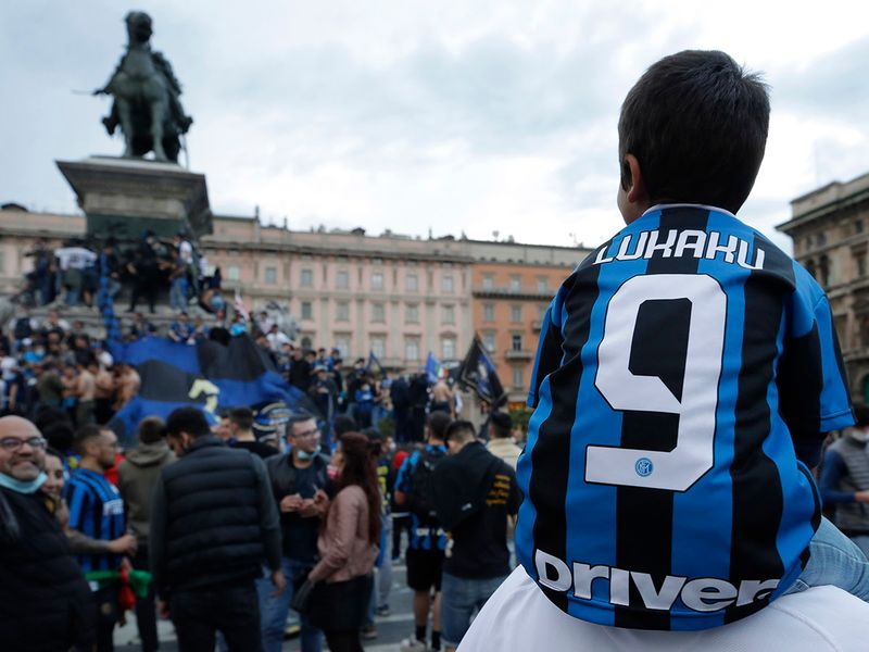 Inter Milan fans celebrate and shout slogans in Piazza Duomo square in front of the gothic cathedral after Inter Milan won its first Serie A title in more than a decade after second-placed Atalanta drew 1-1 at Sassuolo.