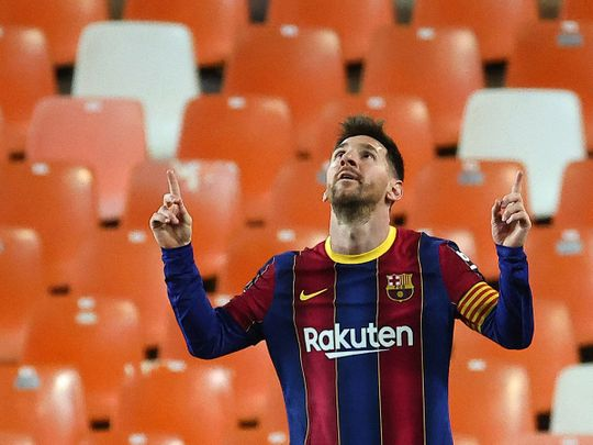 Messi celebrates two goals against Valencia as Barcelona wins 3-2.
