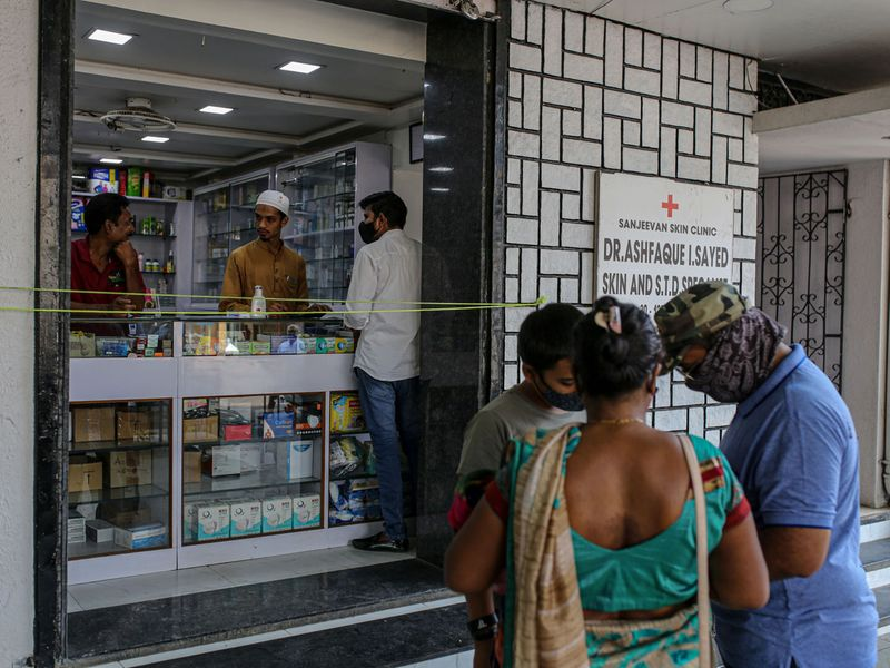 Customers outside a medical store in Pune, Maharashtra, India, on Wednesday, May 5, 2021. SerumInstitute of India Ltd., the worlds largest vaccine maker based in Pune, will deliver 220 million doses to India's vaccine-starved federal and state governments over the next few months, which can cover 8% of the country's population.
