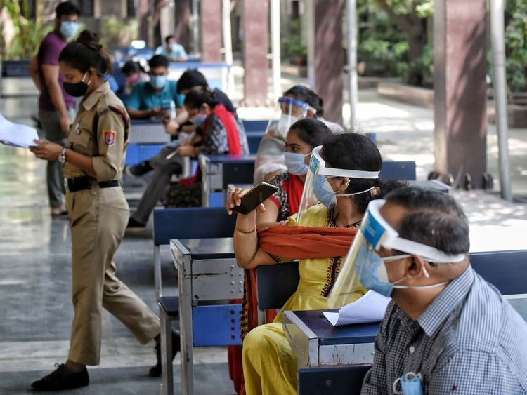 People wait in a queue to receive the COVID-19 vaccine dose,  at a government school in New Delhi on Wednesday.