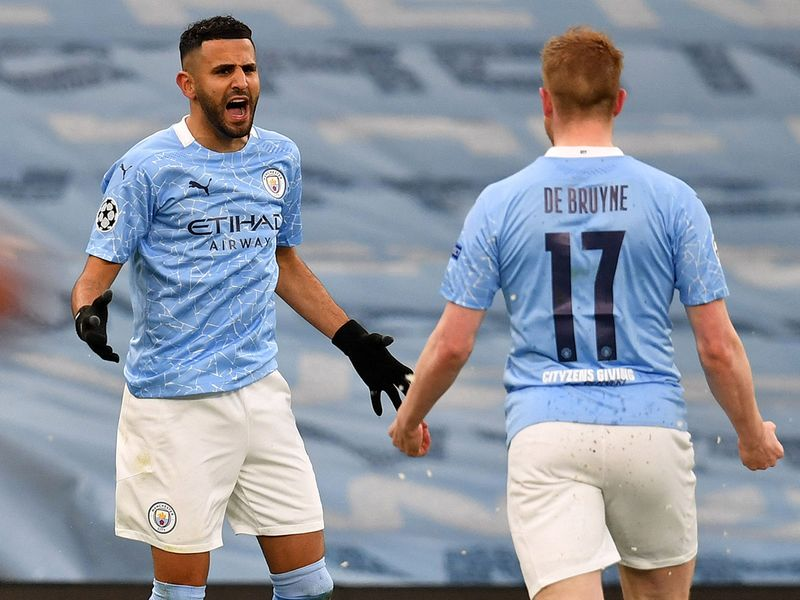 Manchester City's Algerian midfielder Riyad Mahrez (L) celebrates scoring the opening goal with Manchester City's Belgian midfielder Kevin De Bruyne during the UEFA Champions League second leg semi-final football match between Manchester City and Paris Saint-Germain (PSG) at the Etihad Stadium in Manchester, north west England, on May 4, 2021.