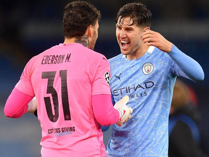 Manchester City's Brazilian goalkeeper Ederson (L) and Manchester City's English defender John Stones celebrate after winning the UEFA Champions League second leg semi-final football match between Manchester City and Paris Saint-Germain (PSG) at the Etihad Stadium in Manchester, north west England, on May 4, 2021.