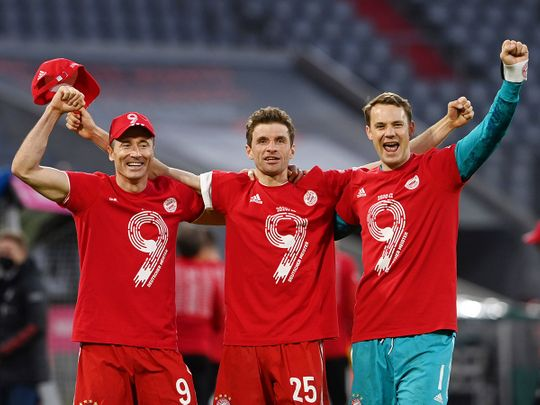 Bayern Munich's Thomas Muller, Manuel Neuer and Robert Lewandowski celebrate after the match after winning the Bundesliga.