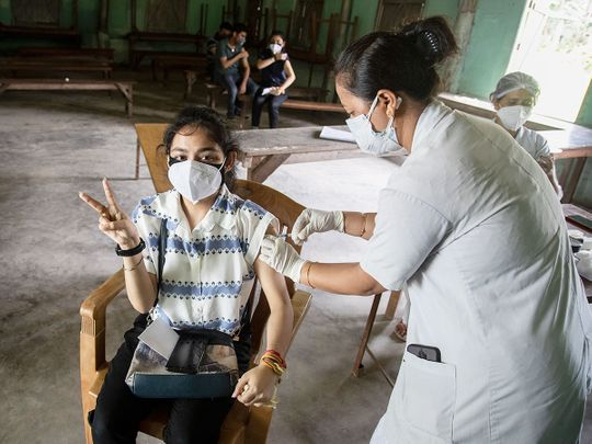A woman getting vaccinated with a dose of COVAXIN against the coronavirus gestures to camera in Gauhati, Assam.