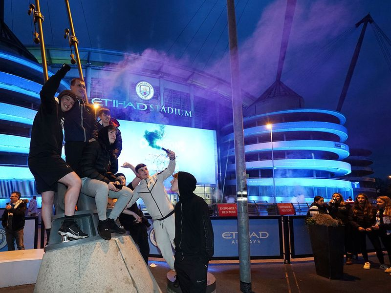 Manchester City fans celebrate winning the English Premier League title