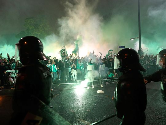 Riot police face off with Sporting fans as supporters bring down fences set along the road