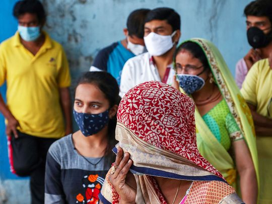 People wearing masks wait to test for COVID-19 at a hospital in Hyderabad.