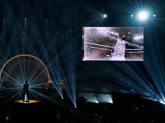 A image of Kobe Bryant is projected on a video screen above the stage as Ne-Yo sings at the 2020 Basketball Hall of Fame ceremony