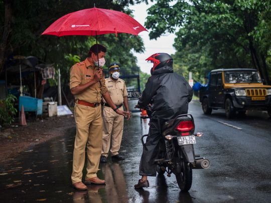 A police officer holds an umbrella to protect himself from the rain as he enforces a lockdown to curb the spread of the coronavirus in Kochi, Kerala state, India, Sunday, May 16, 2021.