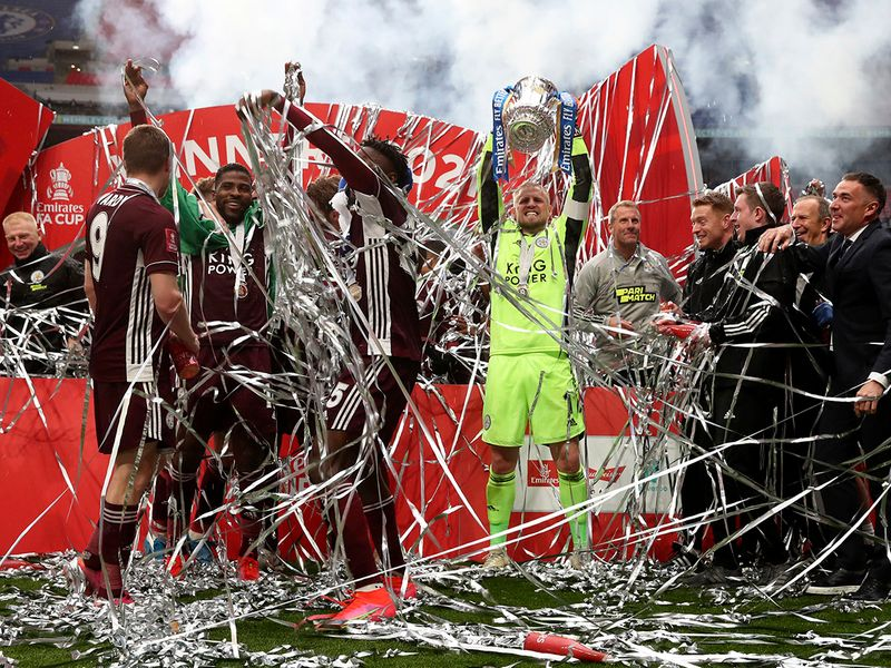 Leicester's goalkeeper Kasper Schmeichel, center, celebrates with the trophy after winning the FA Cup final.