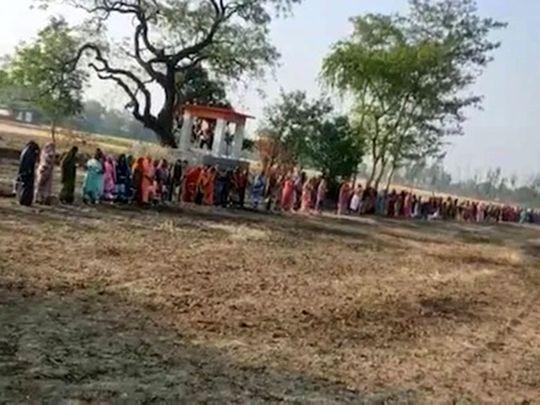 Women line up to pray to Corona Mai in Kushinagar