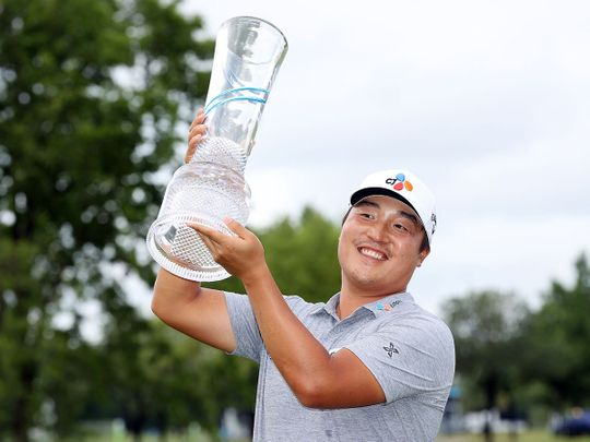 KH Lee of South Korea celebrates with the trophy after winning the AT&T Byron Nelson