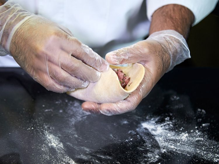 Close the dough from all sides, by folding it sideways, inwards and outwards to cover the filling in completely