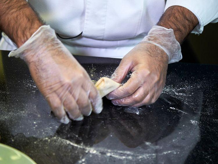 Folding dough to begin filling the arayees paratha