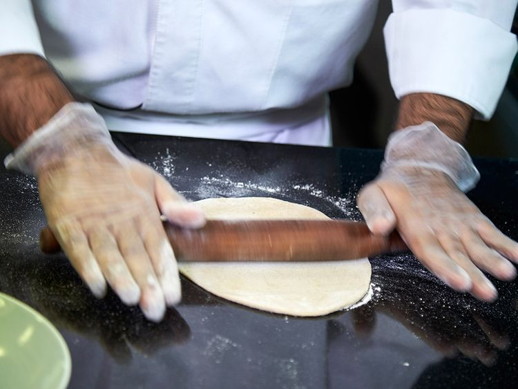 Rolling the dough with a rolling pin for arayees paratha