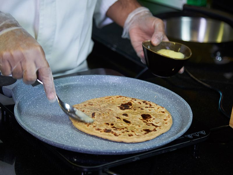 Smearing ghee on arayees paratha