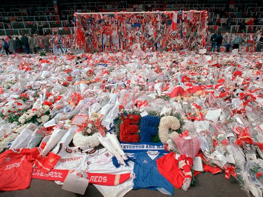 Thousands visited Anfield Stadium to pay their respects as flower tributes cover the 'Kop' end of the field, in Liverpool, on April 17, 1989, following April 15, when fans surged forward during the FA Cup semi-final between Liverpool and Nottingham Forest at Hillsborough Stadium in Sheffield, when the crash barriers gave way, killing 96 Liverpool fans and injuring over 200 others.