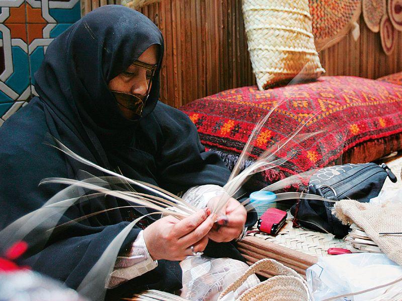 Emirati woman weaving straw baskets