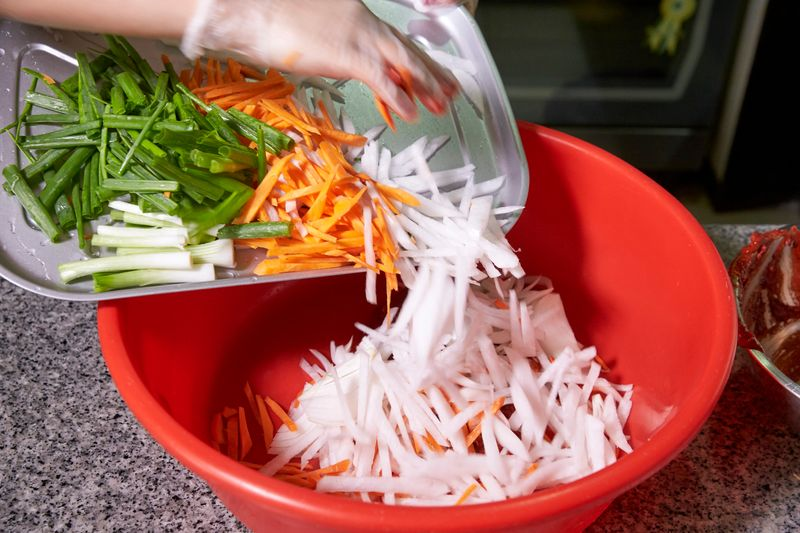 Transfer the radish, carrots and spring onions to a large tub