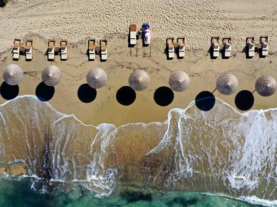 A woman enjoys the sun at Plaka beach on the Aegean island of Naxos, Greece.