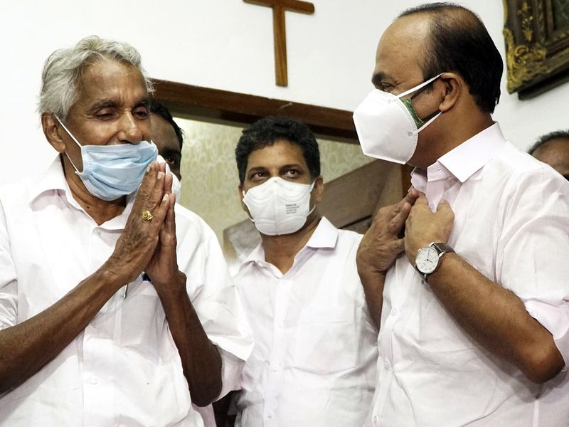Senior congress leader Oommen Chandy (L)  greets newly appointed opposition leader of Kerala Assembly VD Satheesan in Thiruvananthapuram, Sunday, May 23, 2021.