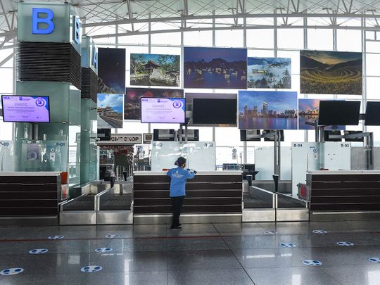 A cleaner cleans a check-in counter area of Noi Bai International Airport in Hanoi.