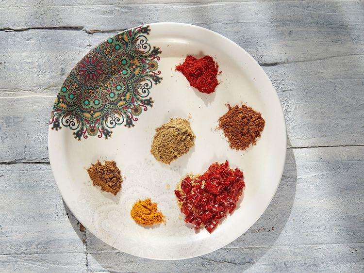Indian Spices - [Clockwise] red chilli powder, jeera powder, dried red chilly, turmeric, garam masala, coriander powder