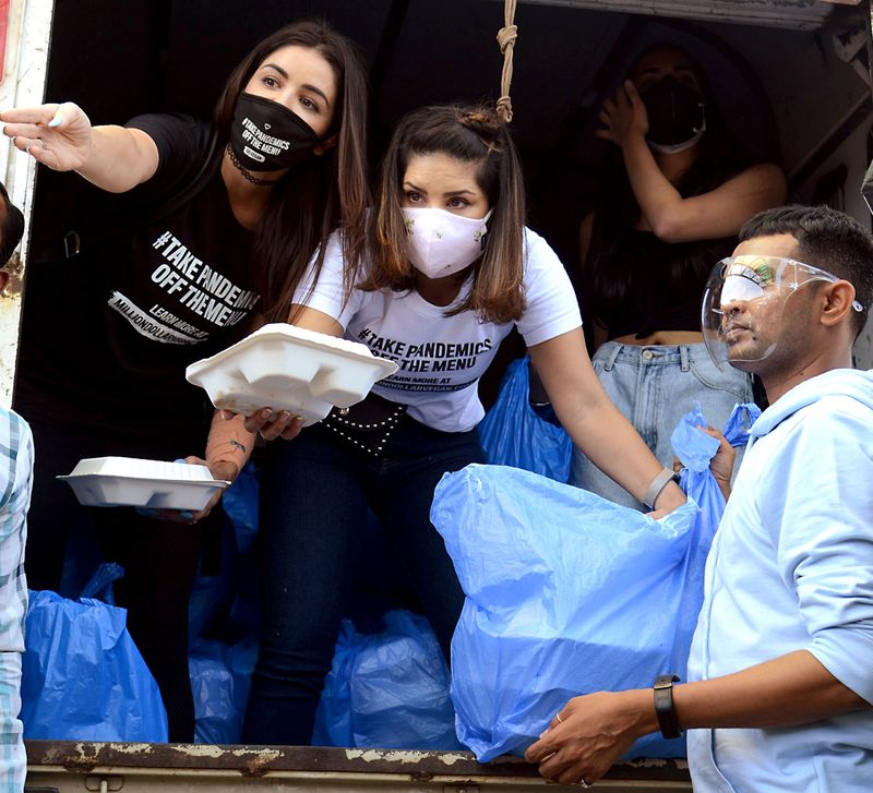 Bollywood actress Sunny Leone distributes food packets to needy people, in Mumbai on Sunday.