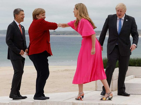 Britain's Prime Minister Boris Johnson (R) and his wife Carrie Johnson welcome Germany's Chancellor Angela Merkel and her husband Joachim Sauer