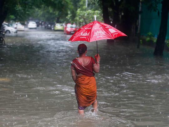 A woman walks through a flooded street during heavy rains in Mumbai