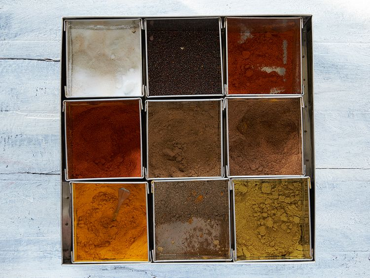 Spice box containing (from top left) salt, mustard seeds, red chilli powder, fish masala powder, garam masala powder, cumin powder, turmeric powder, Arabic spice mix