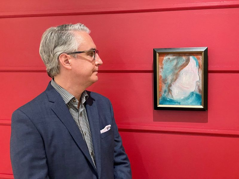 A handout photo released on June 15, 2021, courtesy of the auction house Cowley Abbott shows Canadian Art Specialist Rob Cowley looking at a painting by British pop icon David Bowie in Toronto, Canada