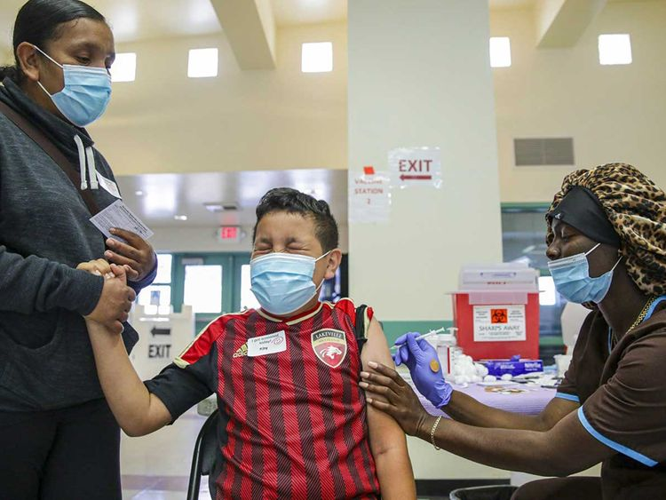 Christiana Neri, 38, holds her 13-year-old son Ivan Hernandez as Sequoia Hutton administers the Pfizer COVID-19 vaccine at a mobile vaccine clinic held for people age 12 and over at Roosevelt Park on Friday, May 14, 2021, in Los Angeles.