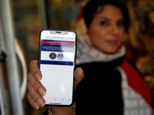 An Iranian woman shows on her mobile phone a statement declaring the website of Iran's English-language television station Press TV