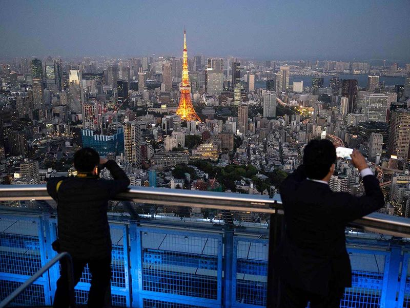 Men taking pictures of Tokyo Tower from the rooftop of the Roppongi Hills Mori Tower in Tokyo