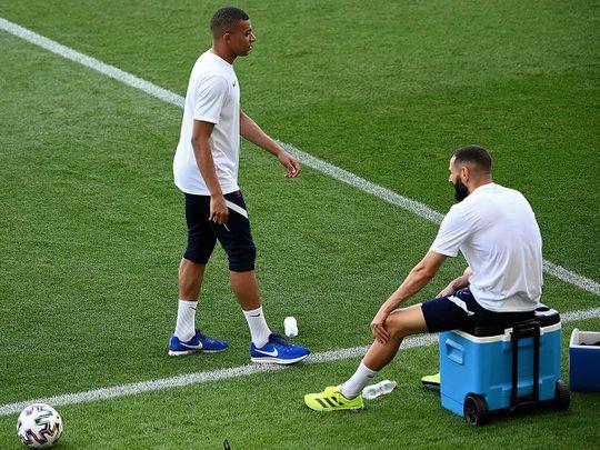 French strikers Kylian Mbappe and Karim Benzema take a break in training