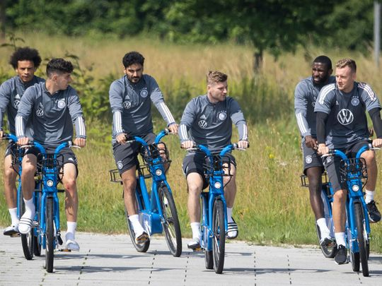 Germany's Leroy Sane, Kai Havertz, Ilkay Guendogan, Timo Werner, Antonio Ruediger and goalkeeper Bernd Leno ride their bikes during a training session